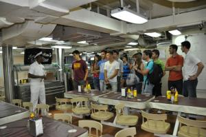 A U.S. Marine gives alumni a tour of a U.S. Navy ship