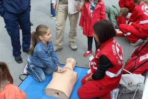 A young participant practices CPR on a model victim.
